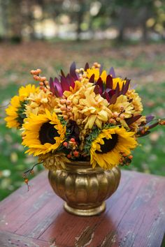 Sunflowers, maroon leucandendron, yellow winterberry branches, oriental bittersweet, and rust-colored mums arranged in a gold vase add a touch of fall to any Thanksgiving table. Fall Wedding Colors, Yellow Wedding, Dream Wedding, Sunflower Wedding Centerpieces, Gold Centerpieces, Natural Fall Decor, White Mums, Sunflower Baby Showers, Baby Shower Yellow