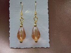 14kt Gold Plated Earrings with a Peach Glass Drop.  -  Materials: Peach Glass Crystals, 14kt Gold Plated Ear Wires, Tiny Gold Coloured Bead, Gold Plated Headpins