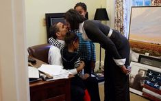 Kisses for the Mrs.! Michelle and Barack share a moment of love in front of their girls Image Credit: Pete Souza