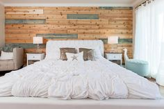Reclaimed pine provides a warm, rustic backdrop for this room's modern king-size bed. Mixing sanded pieces with worn, blue-gray boards adds additional visual interest.