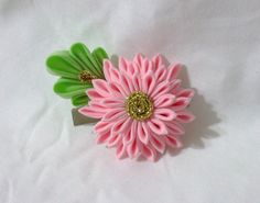 This cute hair accessory is crafted from cotton fabric and features a small pink kiku kanzashi and leaf. The flower measures approx. 2 1/4 by 1 3/4