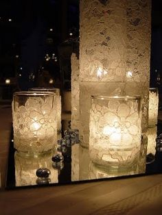 Candles and votives on mirrors and the lace adds a nice vintage touch. Perfect for a winter wedding.