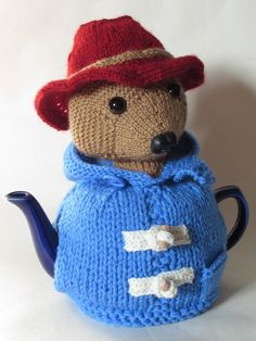 Michael Bond's, Paddington Bear from Darkest Peru has now been revisaged as a charming tea cosy. The Paddington tea cosy has a blue duffel coat with wooden toggles and a big floppy red hat for Paddington to hide his marmalade sandwich under. Paddington looks so cute as a tea cosy, and the roundness of a teapot lends itself to Paddingtons build. The Paddington bear tea cosy can bring a touch of childhood charm to any teatime, so will you look after this bear?This tea cosy is knitted on two...