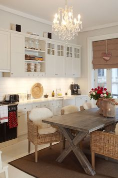 ~earthy colors~kitchen decor~white cabinets, wicker chairs, wooden dining table, chandelier, and natural colored window shade~ Kitchen Dinning, New Kitchen, Kitchen Decor, Cozy Kitchen, Kitchen Island, Dining Room, Eclectic Kitchen, Modern Kitchen Design, Estilo Interior