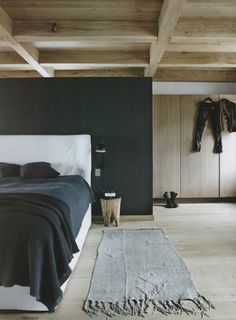 Rustic chic | dark grey  bedhead partly hidding wooden walk-in closet, wooden bedside table