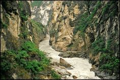 China-TIGER LEAPING GORGE HIKE   Located 60 km north of Lijiang, Tiger Leaping Gorge is a canyon on the Yangtze River. Around 15 km in length, the gorge passes between Jade Dragon Snow Mountain (Yùlóngxuĕ Shān) (5,596 m) and Haba Xueshan (Hābā Shān) (5,396 m) through a series of rapids surrounded by steep 2000 metre cliffs.   Legend says that in order to escape from a hunter, a tiger jumped across the river at it's narrowest point (25 metres), subsequently providing the inspiration for the…