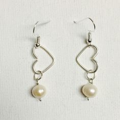 Made a pair of minimalist silver dangling heart earrings with freshwater pearls!