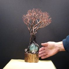 Is it Spring yet? Maybe a good wish :) Wire Tree Of Life Grove leading the way as the entourage of 7 are dressed in black roots and various shades of copper. Their toes wrapped around a 65 mm green beautiful Fluorite Sphere and 2 white and clear Quartz Crystal clusters. The sculpture is mounted on a nature Aspen wood base with a light clear coat with felt pads. Handmade unique art.  Harmony of Spring..as the group seems to be looking forward to Spring and have gathered to do a little…