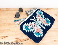 Combinando el crochet y el punto de cruz es posible hacer originales y coloridos diseños como es el caso de este clutch de trapillo y punto de cruz.