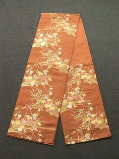 This is a Fukuro obi with 'kiku'(chrysanthemum), iris and 'hagi'(Japanese bush clover) patterns, which are woven on the bright reddish brown background.