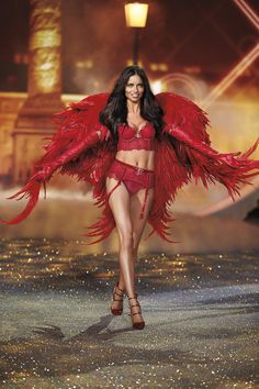 Adriana is ravishing in larger-than-life red wings.