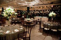 Decoração para recepção com arranjos altos nas mesas dos convidados, velas penduradas.  Mesas com e sem toalhas