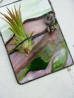 This stained glass panel air plant holder has some pretty green and pink glass! This lovely panel is 6.75 inches tall and 5 inches wide and is perfect for an office, bedroom, kitchen, (great that hard to buy for friend or relative) or bathroom. It is ready to hang and is meant to hang on the wall (near a window) but cant have direct sun (except during the winter months).  It gives the effect of a landscape view and is a great way to bring color to your home or office space. The complementary…