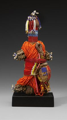 Africa | Beaded doll from the Kirdi people of Cameroon | Wood, beads, West African coins, leather sac, orange, blue, red glass beads, shells, string | 20th century