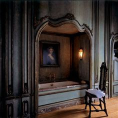 At Axel Vervoordt's Belgian château, baths are drawn in an intimate alcove adorned by Italian 18th-century boiserie. Nearby, an antique Baroque chair faces a portrait — attributed to Thomas Gainsborough — depicting one of King George III of England's nine daughters #Halloween