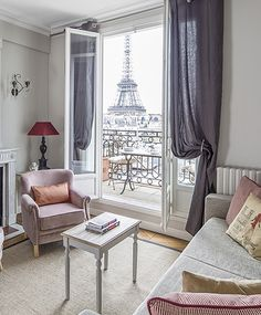Romantic pink accents in the living room, with a picture-perfect view of the Eiffel Tower. Apartment rental by Paris Perfect.
