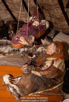 Image of nyaka, an elderly nenets woman, rocks her grandaughter in a cradle inside their reindeer skin tent.tambey tundra, yamal peninsula, western siberia, russia. by ArcticPhoto