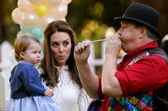 Princess Charlotte watches intently as an entertainer blows her a balloon animal at the ch...