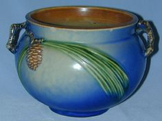 Description: A most beautiful and rare Jardinière made by the Roseville Pottery Company. The jardinière is in the blue pine cone pattern. The piece has two small handles which are cast in the form of