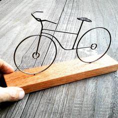 Bicicleta de arame pintado na cor acobreada em base de madeira