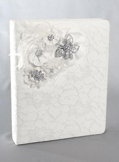 Genevieve Wedding Memory Book covered in satin that is available in white or ivory. It is then decorated with a matching lace overlay. The top left corner is decorated with a cluster of satin flowers, lace, feathers, pearl strands, and rhinestone brooches. Inside, the memory book has a 3-ring brass binder with elegant embossed pages to record all your favorite memories from the proposal to your honeymoon.