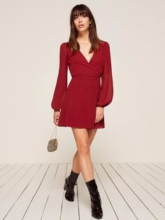 Let your legs say hello. This is a mini length, wrap dress with long sleeves and a v neckline.