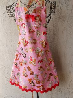Party girls apron with sweetheart neckline and bow reverses to beige with pink rosebuds has red ric rac on the hemline