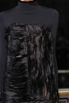 Dress with layered horizontal & vertical shredded fabric panels creating rippling black textures; fashion details // John Galliano