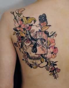Delicate floral and skull design tattoo with black and grey shading and shades of pink and green as accents.