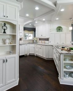 The redesign of the kitchen space required a spacious plan that would accommodate multiple cooks, maximize function and provide adequate storage. Dark brown wood floors provide a beautiful contrast to the kitchen's all-over white cabinetry.