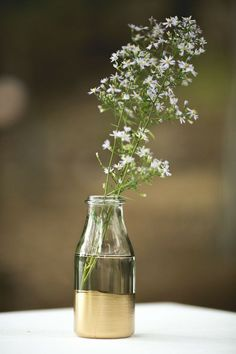 Simple yet chic - gold dipped bottle and a branch of baby's breath.