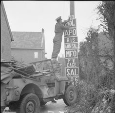 A military policeman of 108 Provost Company stands on the bonnet of his jeep to fix a road sign, The Netherlands, 1 January 1945.