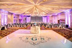 We LOVE this wedding at Venuti's. This reception looked amazing with ceiling draping, fairy lights, a white dance floor, vinyl monogram, purple uplighting, and crystal curtain backdrop.