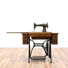 This antique sewing machine table is featured in a solid wood with a dark oak finish. This American traditional style sewing machine has a cast iron base, 5 drawers, and carved laurel motifs. Perfect for home projects! #americantraditional #tables #consoletable #sandiegovintage #vintagefurniture