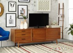 Clever placement of black gallery frames above an attractive Mid-Century media console allows this large TV to disappear into the background—becoming just another piece of framed art.
