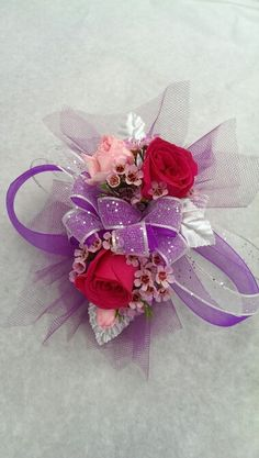 Wrist corsage: hot pink spray roses, pink elegance (mini carnations), pink waxflower with purple and silver trim
