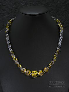 FREE SHIPPING within the USA!    Yellow and Grey.    A sleek, beaded Kumihimo necklace with lampwork Boro glass focal beads: fIve graduated marbles by Unicorne Beads in a colorful swirl design. Each bead is individually hand-made and colorful, with yellow as the main hue. Complimenting the focal beads are braided ropes of cylinder, hex and seed beads in matte nickel, bronze and iridized topaz. Silver-plated bullet end caps and a lobster clasp complete the design. Kumihimo is an ancient…