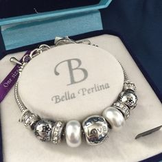 Silver Charm Bracelet Never been taken out of the box! This is a silver bracelet with an adjustable clasp. It has 9 beads of various decorations. Bella Perlina Jewelry Bracelets