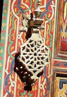 Brass door knocker on brightly painted Asian door