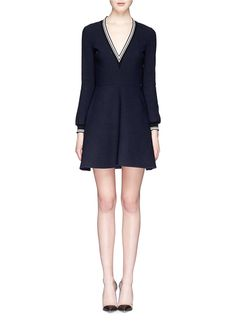 Much adored for its inherently sophisticated sculpts, VICTORIA, VICTORIA BECKHAM puts its chic aesthetics to the test with this sports-oriented dress. Meticulously implanting contrast ribbed knit trims, this piece wows both the frame and eyes with its simple architecture and micro bouclé texture.