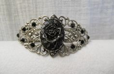 I found 'Antique Silver Filigree Bracelet. Hand Painted Black & Silver Rose Cameo. Jet Black Swarovski Crystal accents' on Wish, check it out!
