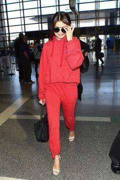 Atriz andando em aeroporto com um conjuto de moletom vermelho