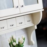 White Painted Kitchen Remodel: Apothecary drawers from #DuraSupreme #Cabinetry shown with in Maple with Antique White painted finish are shown in this cottage styled #kitchen design. – Find more ideas like this at DuraSupreme.com
