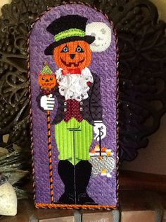 Labors of Love Mr. Pumpkin head is stitched masterfully by Karen Kugel of Park Avenue Nedlpt. A 2016 class piece, call for details.
