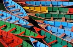 TEOMONTANA's Photoblog   Brightly colored wooden boats line the shores of Phewa Lake in Pokhara,Nepal. Water taxis are painted in the colors of Tibetan prayer flags and take visitors as well as locals to the pagoda of peace.