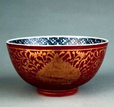 Ming dynasty, Jiajing period, AD1522–1566 Porcelain bowl, decorated inside in underglaze blue with a chrysanthemum and a butterfly. It is covered outside with an iron-red ground and cut out gold foil which was incised and fired at a low temperature. This decorative technique is known as kinrande, (gold brocade style). @ The British Museum