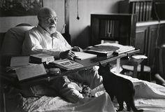 Henri Matisse trabajando en la cama en 1949, en compañía de sus gatos… buena compañía.