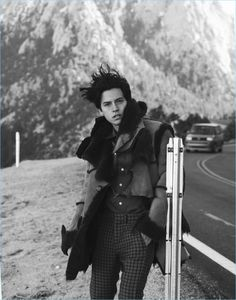 Taking to the side of the road, Cole Sprouse dons a Coach coat and pants with a Roberto Cavalli shirt.