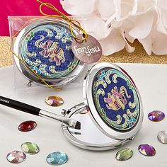 """One 2 3/4"""" diameter Indian Elephant Themed Metal Compact Mirror. These are perfect party favors. The mirrors are crafted from silver metal and feature a bold hot pink elephant on a deep blue and gold"""