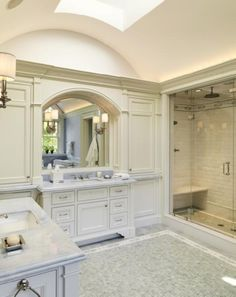- curved ceiling skylight ivory built-in bathroom cabinets twin single bathroom cabinets marble countertops arched mirrors seamless glass shower subway tiles shower surroud mosaic tiles floor